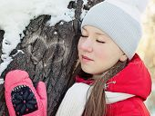 A girl in winter at tree with closed eyes