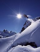 image of winter sport  - Snowboarder jumps high in dramatic mountain scene with white snow and clear blue sky - JPG