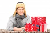 A smiling guy with hat and neckwear lying on a carpet near presents isolated against white backgroun