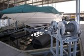 stock photo of canopy roof  - Expensive pleasure boat safely stored under canopy on a hyrdolic lift in a dock