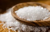pic of crystal salt  - Close up of sea salt with wooden spoon on a background of sea salt - JPG