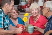 stock photo of patron  - Group of four happy senior citizens at restaurant - JPG