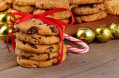 A stack of holiday chocolate chip cookies tied with a red ribbon in front of jingle bells , candy cane, and a platter of assorted baked treats. Horizontal format with shallow depth of field.