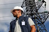 stock photo of electricity pylon  - Worker standing in front of an electricity pylon - JPG
