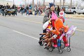 BROKEN ARROW, OK-DECEMBER 8: A seller of inflatable toys walks ahead of the Broken Arrow Christmas Parade on December 8, 2012.