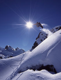 foto of winter sport  - Snowboarder jumps high in dramatic mountain scene with white snow and clear blue sky - JPG