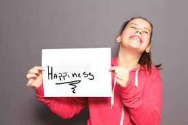 picture of ecstacy  - Fun Happiness concept with a young girl holding up a handwritten sign saying Happiness and tilting her head back with a cheeky ear to ear grin - JPG
