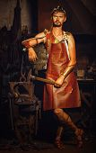foto of anvil  - Hephaestus blacksmith in a leather apron in the blacksmith with hammer and clippers anvil - JPG