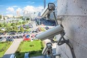 stock photo of supervision  - Video surveillance cameras on a wall looking at street parking area - JPG