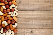stock photo of hazelnut  - Mix of hazelnuts almonds and cashew nuts on wooden background - JPG