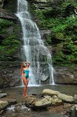 Beautiful slim fitness model posing sexy in front of waterfalls wearing one-piece blue swimsuit