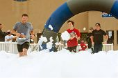 Male Runners Run Through Foam At Finish Line Of Race