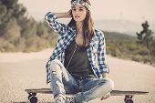 stock photo of skateboard  - Beautiful young woman sitting over a skateboard - JPG