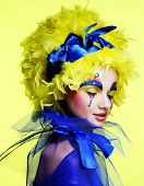 Young woman with yellow wig feather. Holiday theme.