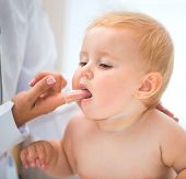 picture of teething baby  - doctor cleans baby mouth with a special brush - JPG