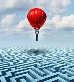 stock photo of maze  - Rise above adversity solution Leadership with a businessman flying and soaring over a complicated maze with the help of a hot air balloon as a business concept of innovative creative thinking for financial success - JPG