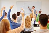 Students lifting hands in college class with teacher on whiteboard