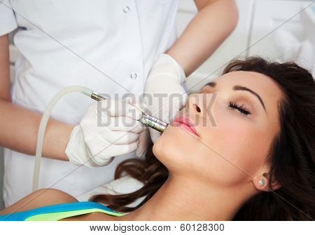 Woman getting laser face treatment in medical spa center, skin rejuvenation concept poster