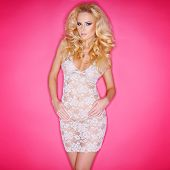 Sexy young blond woman with a shapely figure in a see-through lacy white dress against a pink backgr