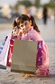 Smiling Cute Girl Squatting With Shopping Bags