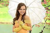 Portrait of young woman in Victorian dress holding umbrella outdoors