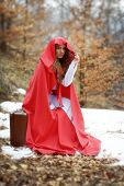 beautiful woman with red cloak sitting on suitcase