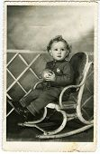 KURSK, USSR - CIRCA 1970s: An antique photo shows portrait of a little boy Kinky little boy sitting