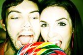 Couple Biting Into Lollipop