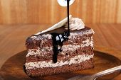 foto of cream cake  - sweet brownie chocolate cream cake topped with white chocolate and cream with chocolate with chocolate sauce on wooden background - JPG