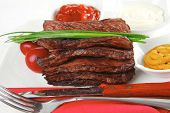 roast red beef meat fillet with red hot pepper with ketchup mayonnaise and mustard on plate isolated