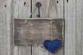 Blank rustic sign with blue heart and iron key