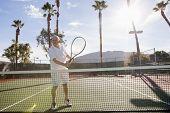 Senior male tennis player holding racket on court