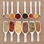 Herb and spice selection in metric measuring spoons and scoops over hessian