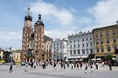 Tourists visiting main market square in front of St. Mary's Basilica in Krakow Poland