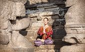 stock photo of namaste  - Woman in lotus pose with hands in Namaste gesture sitting near Shore temple Mamallapuram Tamil Nadu India - JPG
