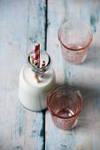 Retro Milk Bottle With Pink Glasses And Striped Drinking Straw Background