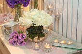 Table decorated with candles and white roses