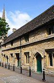 stock photo of church-of-england  - Almshouses with St John the Baptist church to the rear Burford Oxfordshire England UK Western Europe - JPG