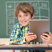 Handsome Little Boy Using A Tablet In School