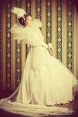 Beautiful fashion model in the refined white dress and elegant hat. Vintage style. Sepia. Art project.