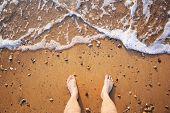 Man's Legs On The Sand Beach