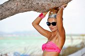 Young Attractive Woman In Sunglasses And Bikini Under Tree Brach In Summer Vacation