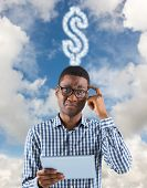 Young businessman thinking and holding tablet against blue sky with white clouds