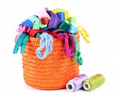 Round orange box full of multicoloured threads and everything necessary for sewing on white backgrou