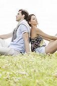 Relaxed young couple sitting back to back in park