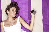 Relaxed woman listening to music through MP3 player using headphones while lying on picnic blanket