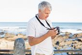 Casual mature man looking at his camera the sea on a sunny day
