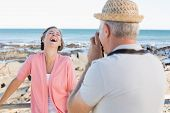 stock photo of take off clothes  - Happy casual man taking a photo of partner by the sea on a sunny day - JPG
