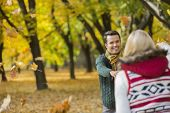 Happy couple playing with autumn leaves in park
