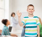 childhood, gesture, education and people concept - smiling little boy making ok gesture over group of students in classroom